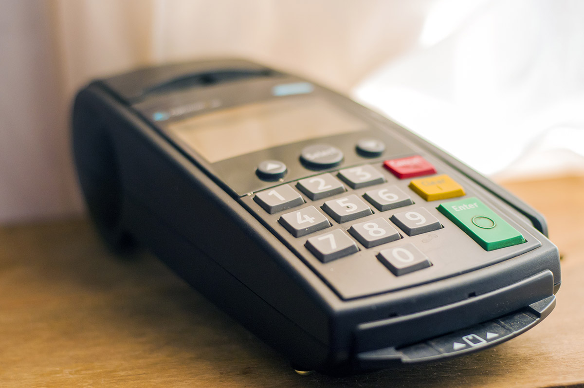 Payment with credit card - businessman holding pos terminal. Pay